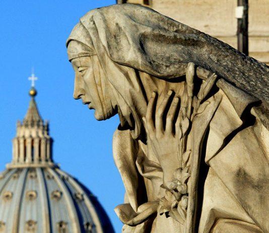 Saint Peter's Basilica is seen behind a statue depicting Saint Catherine © Alessia Pierdomenico : Reuters