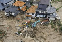 Rescue workers next to houses damaged by a landslide in Hiroshima, Japan. July 7, 2018 © Kyodo / Reuters