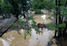 Rescuers stand in a flooded area of a camping as storms and heavy rains sweep across France ( AFP/Getty Images )