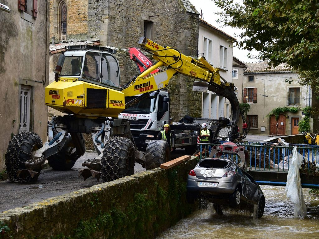 An excavator pulls a car from a river in Villegailhenc, one of the many vehicles that were damaged in flash floods in southwest France overnight.