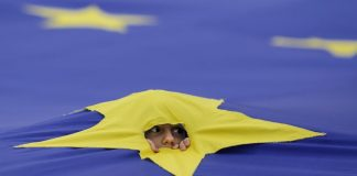 A child peers through a cut made in one of the stars that make up the European Union flag © Reuters / Octav Ganea