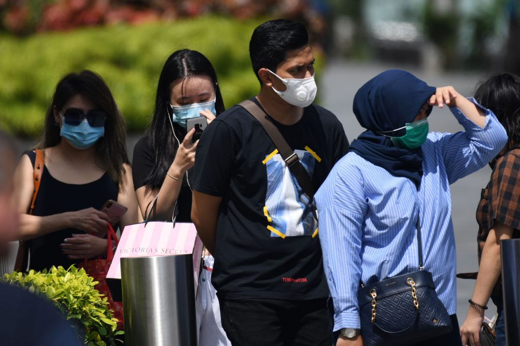 People wearing protective face masks wait at a pedestrian crossing in Singapore on February 4, 2020. Photo by ROSLAN RAHMAN/AFP via Getty Images
