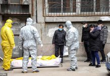 Medics tested the drug mix on a patient who was in a 'serious condition' with the disease and within 48 hours they were declared disease-free. Funeral house workers take the body of a coronavirus victim from their home in Wuhan