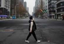 A woman crosses an empty street in Wuhan. The city has been under lockdown since January 23.