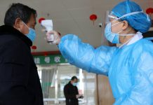 FILE PHOTO: A medical worker takes the body temperature of a man at an entrance to a hospital in Suichuan, China as the country is hit by an outbreak of the new coronavirus. © Reuters / China Daily