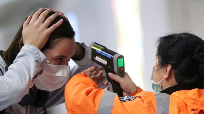 FILE PHOTO: A worker checks the temperature of a passenger arriving into Hong Kong International Airport with an infrared thermometer, following the coronavirus outbreak in China. © Reuters / Hannah McKay
