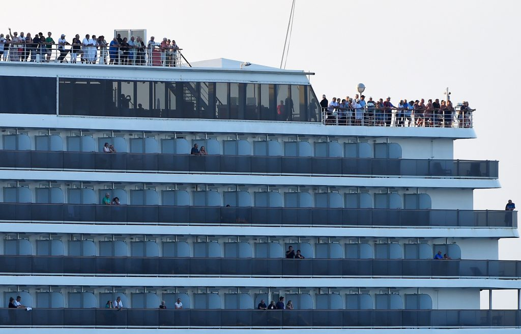 Passengers watch as the Westerdam cruise ship approaches the port in Sihanoukville on Cambodia's southern coast on Feb. 13, where the liner had received permission to dock after being refused entry at other Asian ports due to fears of the COVID-19 coronavirus. Tang Chhin/AFP/Getty Images