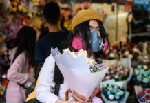 A man wearing a protective face mask as a preventative measure against the coronavirus buys flowers to mark Valentine's Day in Hong Kong on February 14. Philip Fong/AFP/Getty Images