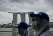 People wearing protective masks walk towards Merlion Park in Singapore on February 12. Maverick Asio/SOPA Images/LightRocket/Getty Images