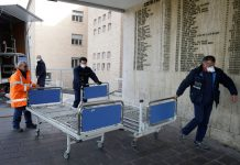 Hospital personnel in Codogno, Italy, carry new beds inside the hospital on February 21. Luca Bruno/AP