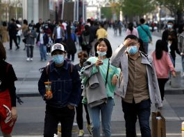 People wearing face masks are seen at a shopping area in Beijing, as the spread of the novel coronavirus slows in China, April 6, 2020. © Reuters / Tingshu Wang