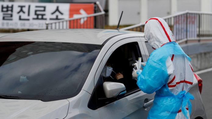 A medical staff member in protective gear tests a patient in Daegu, South Korea during the initial Covid-19 outbreak, March 3, 2020. © REUTERS/Kim Kyung-Hoon