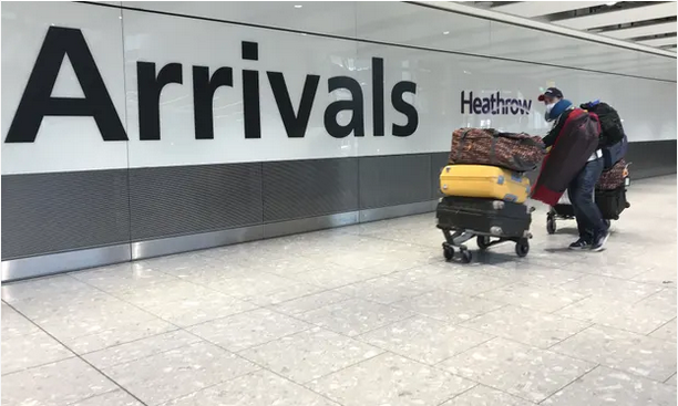 A passenger wears a mask as he arrives at Heathrow Airport. Photograph: Kirsty Wigglesworth/AP